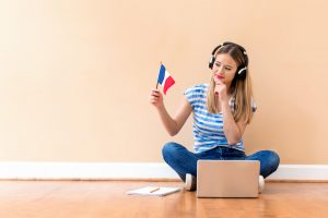 Young woman with French flag using a laptop computer